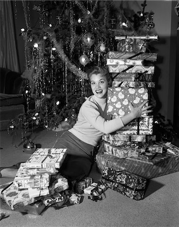 1950s WOMAN SITTING ON FLOOR IN FRONT OF XMAS TREE HOLDING PACKAGES Stock Photo - Rights-Managed, Code: 846-02797885