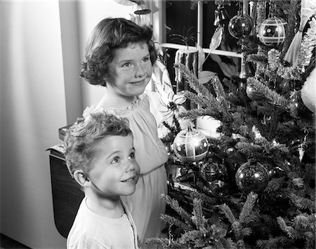 1950s BOY GIRL SMILING UP AT CHRISTMAS TREE DECORATIONS ORNAMENTS PINE FIR CANDLE IN WINDOW WISHING DREAMING Stock Photo - Rights-Managed, Code: 846-02797882