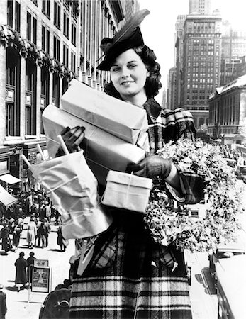 1930s 1940s WOMAN ARMS FULL CHRISTMAS SHOPPING PACKAGES & WREATH COMPOSITE WITH CITY STREET SCENE Stock Photo - Rights-Managed, Code: 846-02797899