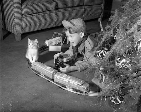1950s BOY IN ENGINEER OUTFIT PLAYING WITH ELECTRIC TRAIN SET BY CHRISTMAS TREE AND KITTEN INDOOR Stock Photo - Rights-Managed, Code: 846-02797914