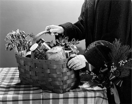 1950s GIFT BASKET FILLED WITH PRESERVES VEGETABLES BREAD FOOD HELD BY FIGURE WITH GLOVED HANDS ON CHECKERBOARD TABLECLOTH Stock Photo - Rights-Managed, Code: 846-02797918