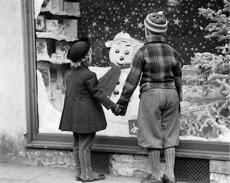 1930s BOY AND GIRL HOLDING HANDS LOOKING AT DECORATED CHRISTMAS WINDOW Stock Photo - Rights-Managed, Code: 846-02797920