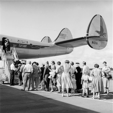 1950s TAIL OF COMMERCIAL AVIATION AIRPLANE ON TARMAC WITH PASSENGERS IN LINE WAITING TO BOARD Stock Photo - Rights-Managed, Code: 846-02791720