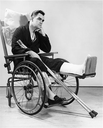 1940s MAN IN WHEELCHAIR WITH CAST ON LEFT LEG HOLDING CRUTCHES Stock Photo - Rights-Managed, Code: 846-02791739