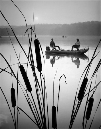 1980s TWO MEN IN BASS FISHING BOAT ON CALM WATER LAKE CATTAILS IN FOREGROUND Stock Photo - Rights-Managed, Code: 846-02791796