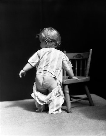 1940s BABY WEARING DROP SEAT PAJAMAS SHOWING BARE BOTTOM LEANING ON CHAIR Stock Photo - Rights-Managed, Code: 846-02791924
