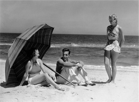 1930s TWO WOMEN 1 MAN SITTING UNDER BEACH UMBRELLA WEARING FASHIONABLE SWIMWEAR Stock Photo - Rights-Managed, Code: 846-02791956