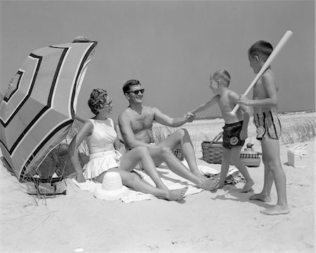 1960s AT THE BEACH TWO BOYS WITH BASEBALL BAT TRYING TO PULL UP FATHER SEATED NEXT TO MOTHER SO HE WILL PLAY WITH THEM Stock Photo - Rights-Managed, Code: 846-02791966