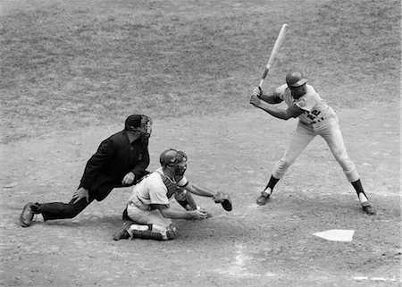 professional baseball game - 1970s SIDE VIEW OF PROFESSIONAL BASEBALL GAME WITH PLAYER AT BAT & CATCHER & UMPIRE BEHIND HIM Stock Photo - Rights-Managed, Code: 846-02792009