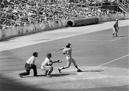 professional baseball game - 1970s SIDE VIEW OF BATTER COMPLETING SWING WITH CATCHER & UMPIRE BEHIND HIM AT PROFESSIONAL BASEBALL GAME Stock Photo - Rights-Managed, Code: 846-02792023