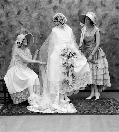 1900 1910s BRIDE WITH ONE BRIDESMAID ON EITHER SIDE HELPING FIX HER WEDDING DRESS Stock Photo - Rights-Managed, Code: 846-02792050