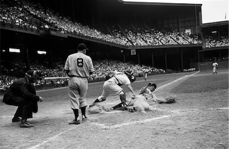 1950s BASEBALL GAME UMPIRE AND PLAYER WATCH AS CATCHER STANDS OVER HOME PLATE BASE AND MAN SLIDES INTO HOME Stock Photo - Rights-Managed, Code: 846-02792064