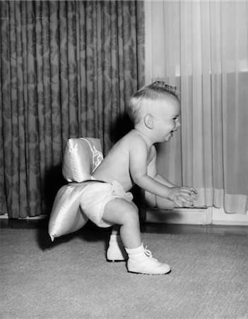 1950s LAUGHING BABY IN DIAPER AND SHOES LEARNING TO WALK WITH A PILLOW TIED TO HIS REAR END Stock Photo - Rights-Managed, Code: 846-02792105