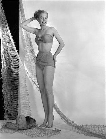 sandi model - 1950s GLAMOUR GIRL POSE IN STUDIO DRAPED WITH FISHING NET WOMAN IN TWO PIECE SWIM BATHING SUIT FASHION STRAPLESS BRA TOP Stock Photo - Rights-Managed, Code: 846-02792137