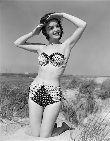 1950s SMILING YOUNG WOMAN KNEELING IN GRASSY SAND WEARING POLKA DOT BIKINI SHADING EYES FROM SUN Stock Photo - Rights-Managed, Code: 846-02792138
