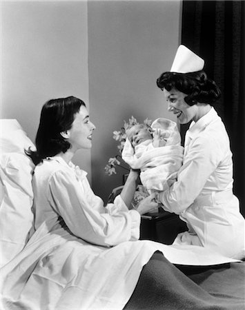 1950s NURSE HANDING NEWBORN INFANT TO MOTHER IN HOSPITAL BED Stock Photo - Rights-Managed, Code: 846-02792170