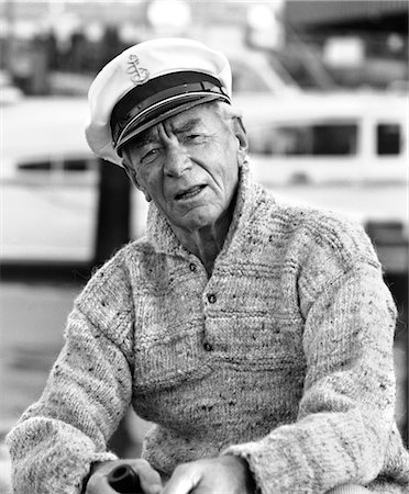 1970s OLDER MAN IN FISHERMAN'S HAT SWEATER HOLDING PIPE SITTING ON DOCKS OUTDOOR Stock Photo - Rights-Managed, Code: 846-02792202