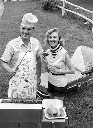 simsearch:846-02793283,k - 1950s COUPLE BACKYARD GRILL COOK HOT DOGS MAN WEARING APRON TOQUE & SKEWERED HOT DOG Stock Photo - Rights-Managed, Code: 846-02792304
