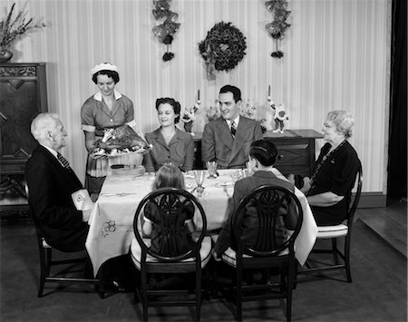 1940s TWO GENERATION FAMILY IN DINING ROOM BEING SERVED CHRISTMAS TURKEY BY MAID Stock Photo - Rights-Managed, Code: 846-02792344