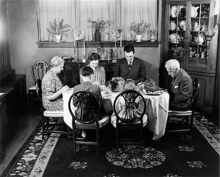 1940s EXTENDED FAMILY SITTING AROUND DINING ROOM TABLE SAYING GRACE BEFORE THANKSGIVING DINNER Stock Photo - Rights-Managed, Code: 846-02792345
