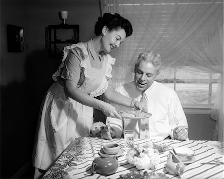 1950s WIFE WEARING APRON SERVING HUSBAND HOME COOKED DINNER BOTH SMILING INDOOR Stock Photo - Rights-Managed, Code: 846-02792341