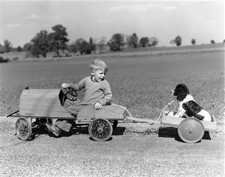 1930s 1940s BOY IN WOODEN TOY CAR PULLING DOG BEHIND IN WAGON Stock Photo - Rights-Managed, Code: 846-02792399