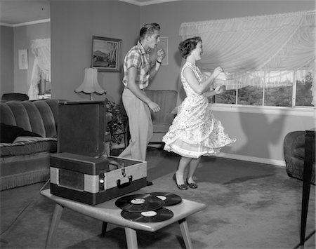 1950s LAUGHING TEENAGE COUPLE DANCING TO THE PHONOGRAPH PLAYING 78 RPM RECORDS IN LIVING ROOM Stock Photo - Rights-Managed, Code: 846-02792414