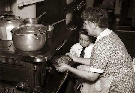 1930s 1940s GRANDMOTHER TAKING PIE OUT OF OVER AS BOY WATCHES Stock Photo - Rights-Managed, Code: 846-02792503