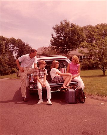 1960s FAMILY SITTING ON BACK STATION WAGON LOADED WITH LUGGAGE FOR VACATION Stock Photo - Rights-Managed, Code: 846-02792579