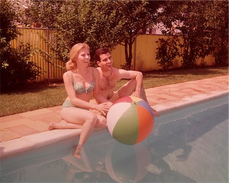 1960s COUPLE SITTING ON EDGE OF SWIMMING POOL Stock Photo - Rights-Managed, Code: 846-02792582