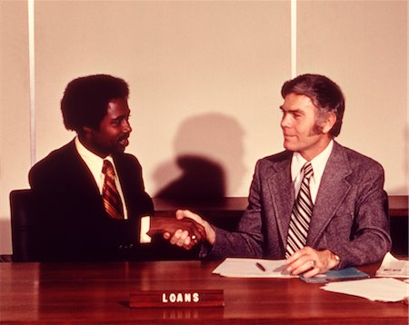 1970s AFRICAN AMERICAN MAN SHAKING HANDS WITH BANK LOAN OFFICER Stock Photo - Rights-Managed, Code: 846-02792666