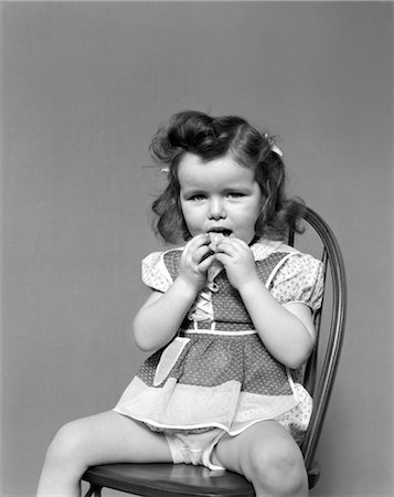 1930s TODDLER GIRL SIT IN WOODEN CHAIR POLKA DOT DRESS SHOWING UNDERPANTS EATING A COOKIE WITH BOTH HANDS VINTAGE Stock Photo - Rights-Managed, Code: 846-02792809
