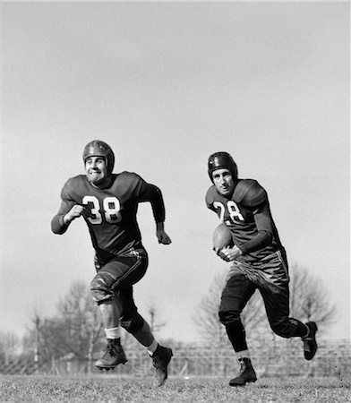 1940s 1950s FOOTBALL PLAYER RUNNING WITH BALL AS DEFENSE TEAM MEMBER RUN AHEAD Stock Photo - Rights-Managed, Code: 846-02792839