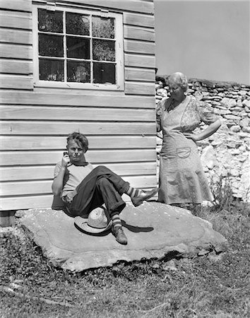 1940s FARM BOY LEANING AGAINST HOUSE SMOKING PIPE WITH GRANDMOTHER LOOKING AROUND CORNER AT HIM WITH HAND ON HIP Stock Photo - Rights-Managed, Code: 846-02792845