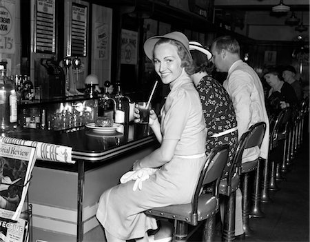 1940s SMILING WOMEN DRESSED IN A CRISP OUTFIT AND HAT HOLDING A GLASS OF SODA WHILE SITTING AT THE COUNTER OF A SODA FOUNTAIN LOOKING AT CAMERA Stock Photo - Rights-Managed, Code: 846-02792924