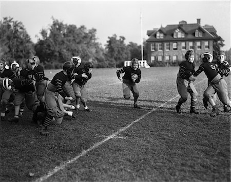 football team - 1930s BOYS SCHOOL FOOTBALL TEAM BOY RUNNING WITH BALL CENTER Stock Photo - Rights-Managed, Code: 846-02792926