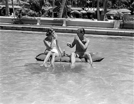 1930s 1940s COUPLE DRINKING WHILE FLOATING IN A POOL ON A RUBBER RAFT AT FLORIDA RESORT Stock Photo - Rights-Managed, Code: 846-02792922