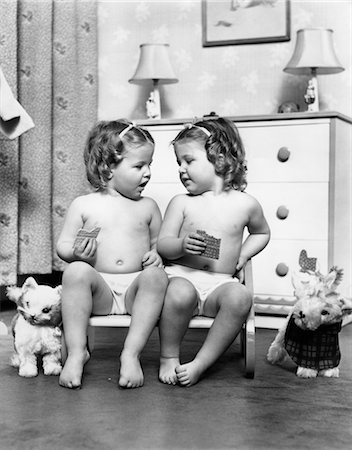 1950s TWIN GIRLS SITTING IN A DOUBLE SEAT WEARING PANTIES ONLY WHILE EATING GRAHAM CRACKERS Stock Photo - Rights-Managed, Code: 846-02792931