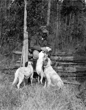 1920s ELDERLY MAN SITTING WITH RIFLE RESTING AGAINST FENCE PETTING ONE OF THREE HUNTING DOGS Stock Photo - Rights-Managed, Code: 846-02792988