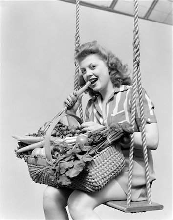 1940s WOMAN SITTING ON A ROPE SWING WITH A WICKER BASKET OF FRESH VEGETABLES ON HER LAP WHILE EATING A CARROT Stock Photo - Rights-Managed, Code: 846-02793010