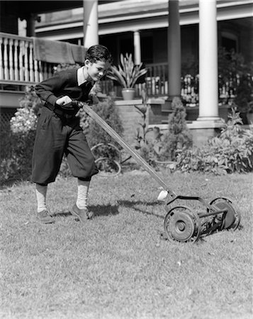 1930s 1940s BOY PUSHING LAWN MOWER WEAR KNICKERS CUTTING THE GRASS CHORE SUMMER JOB YARD WORK Stock Photo - Rights-Managed, Code: 846-02793011