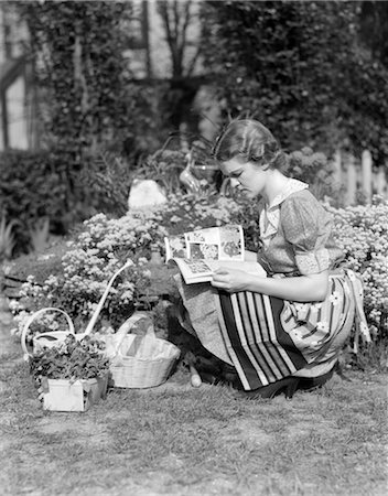 1940s WOMAN DRESSED IN PRINT DRESS AND STRIPED APRON KNEELING IN FLOWERS GARDEN READING A GARDENING MANUAL OR MAGAZINE Stock Photo - Rights-Managed, Code: 846-02793051
