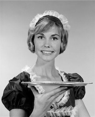 right - 1960s GIRL IN WAITRESS UNIFORM WITH MATCHING LACE HEADPIECE SMILING WHILE HOLDING UP AN EMPTY SERVING TRAY Stock Photo - Rights-Managed, Code: 846-02793080