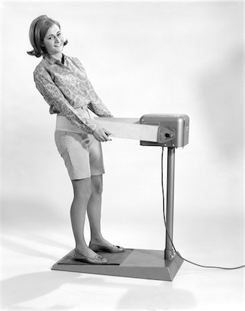 1960s SMILING YOUNG WOMAN STANDING ON WEIGHT REDUCING VIBRATING EXERCISE MACHINE LOOKING AT CAMERA Stock Photo - Rights-Managed, Code: 846-02793093