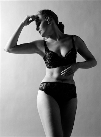 1970s WOMAN WEARING BLACK LACE BRA AND PANTIES HEAD TURNED TO SIDE HAND TOUCHING FOREHEAD ARMS IN GRACEFUL POSE INDOOR Stock Photo - Rights-Managed, Code: 846-02793115