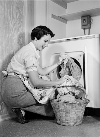 1950s WOMAN KNEELING REMOVING CLOTHES LAUNDRY FROM AUTOMATIC DRYER Stock Photo - Rights-Managed, Code: 846-02793134
