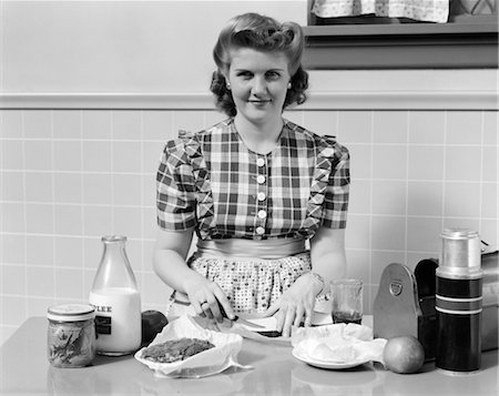 photos of 1940s women in kitchen - 1940s WOMAN SMILING IN KITCHEN MAKING SANDWICHES FOR METAL LUNCH BOX WITH THERMOS BOTTLE Stock Photo - Rights-Managed, Code: 846-02793135