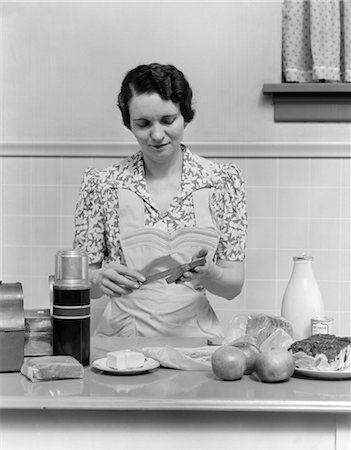 1930s WOMAN HOUSEWIFE IN KITCHEN WEARING APRON MAKING SANDWICH PACKING METAL LUNCH BOX THERMOS APPLES BREAD MILK ON COUNTER Stock Photo - Rights-Managed, Code: 846-02793133