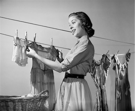 1950s SMILING WOMAN HOUSEWIFE HANGING WASH ON CLOTHESLINE TO DRY Stock Photo - Rights-Managed, Code: 846-02793163
