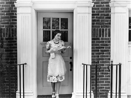 1940s WOMAN IN AN APRON STANDING OUTSIDE DOORWAY HOLDING A QUART OF MILK AND READING NEWSPAPER E Stock Photo - Rights-Managed, Code: 846-02793177